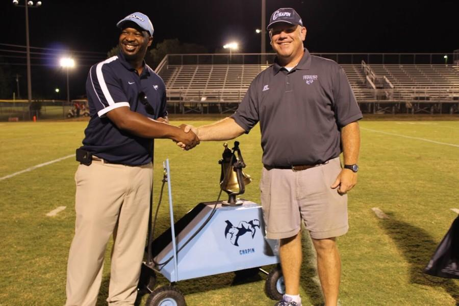 Chapin High School principal Dr. Akil Ross (left) and head football coach Justin Gentry (right) celebrate with the bell after last year's victory over MC.