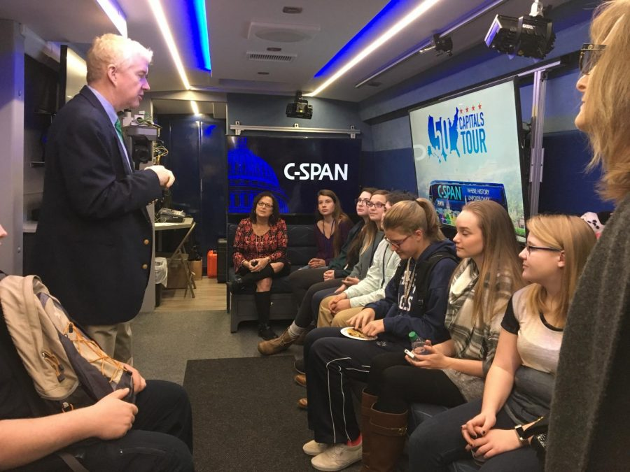 Students listening to a C-SPAN representative on the bus.