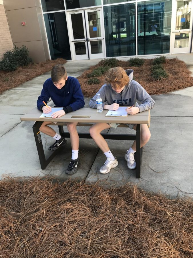 Students from Ms. Alderman's Biology class complete a class assignment in the courtyard.